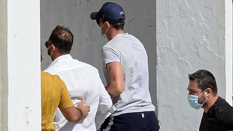 Harry Maguire, in the blue cap, going into the police station on Syros. Pic: Athena Pictures