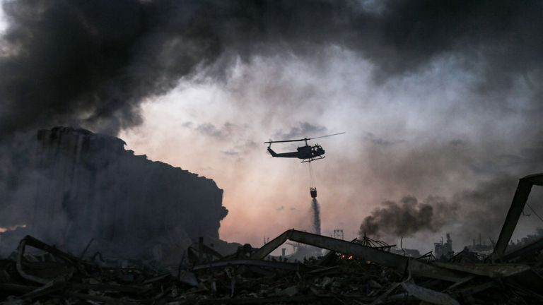 A helicopter puts out a fire at the scene of an explosion
