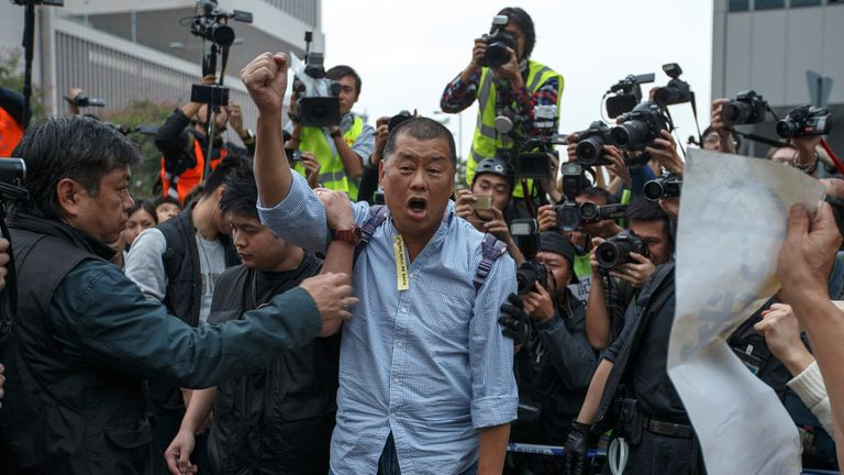 Tycoon and Apple Daily Newspaper owner Jimmy Lai shouts slogan before he is taken away by police officer at an area previously blocked by pro-democracy supporters, outside the government headquarters in Hong Kong, December 11, 2014. Hong Kong authorities started on Thursday clearing the main pro-democracy protest site that has choked roads into the city's most economically and politically important district for more than two months as part of a campaign to demand free elections.