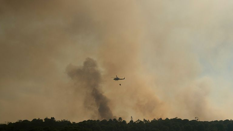 A helicopter drops water over a wildfire raging near El Buitron in Huelva, Spain