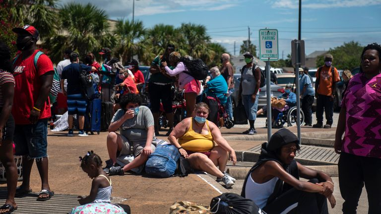 People wait to board a bus as residents evacuate ahead of Hurricane Laura in Galveston, Texas