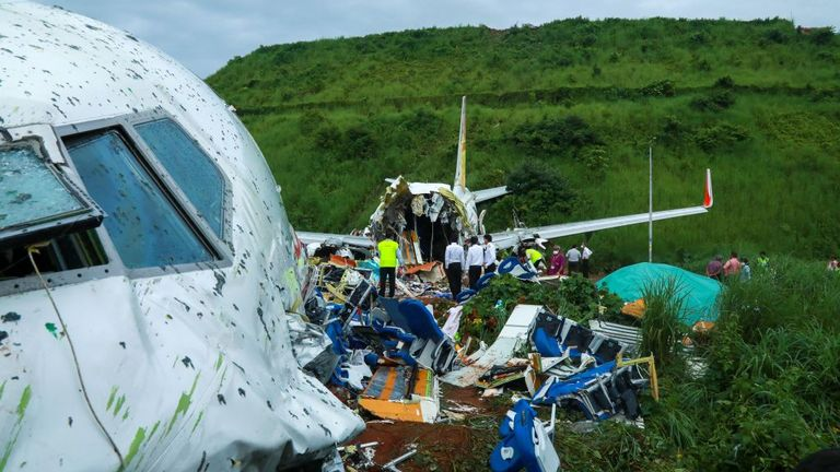 Officials inspect the wreckage of an Air India Express jet at Calicut International Airport