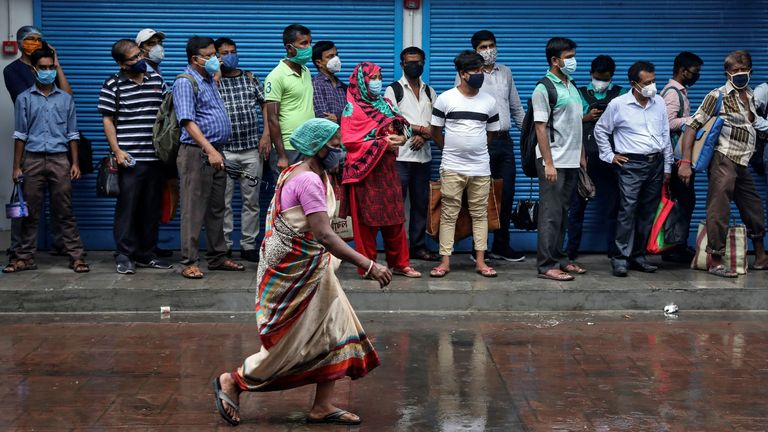 People queue for a bus in Kolkata