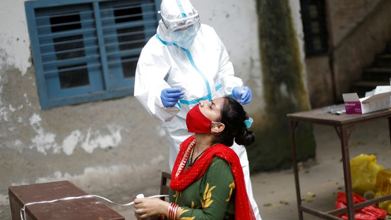 A health worker takes a swab at a test centre in New Delhi