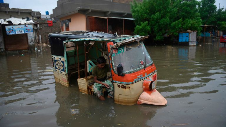 A boy sits in a auto-rickshaw in a flooded area after heavy monsoon rains in Pakistan's port city of Karachi