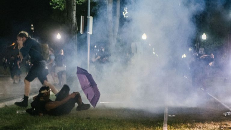 Demonstrators retreat from tear gas fired by police