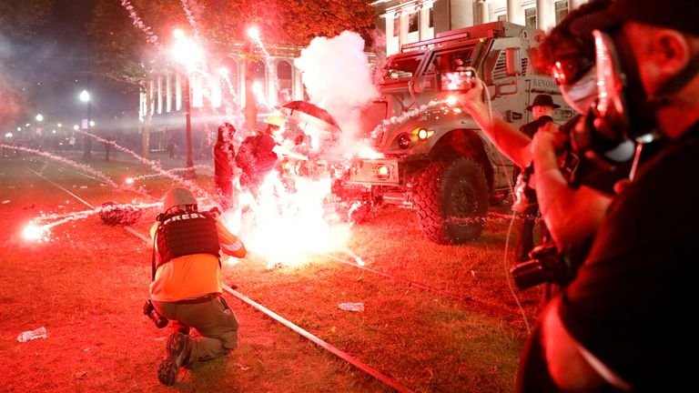 Flares go off in front of a Kenosha Country Sheriff Vehicle as demonstrators take part in a protest following the police shooting of Jacob Blake, a Black man, in Kenosha, Wisconsin, U.S. August 25, 2020. REUTERS/Brendan McDermid TPX IMAGES OF THE DAY