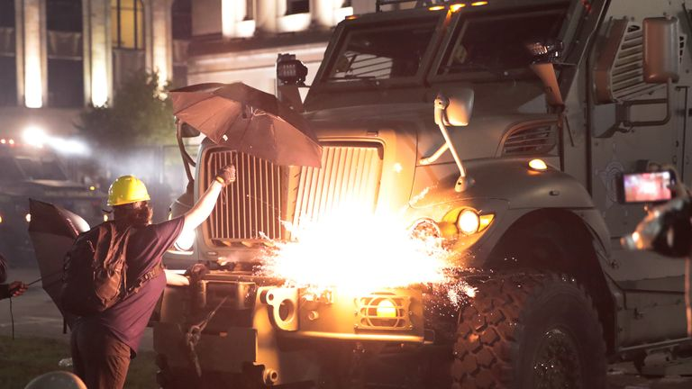 KENOSHA, WISCONSIN - AUGUST 25: An explosive device detonates on the front of an armored vehicle as protesters confront police in front of the Kenosha County Courthouse during a third night of unrest on August 25, 2020 in Kenosha, Wisconsin. Rioting as well as clashes between police and protesters began Sunday night after a police officer shot Jacob Blake seven times in the back in front of his three children. (Photo by Scott Olson/Getty Images)