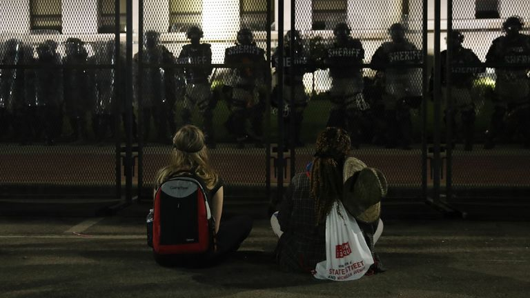 Protesters sit across a fence from riot police outside the County Courthouse in Kenosha, Wisconsin