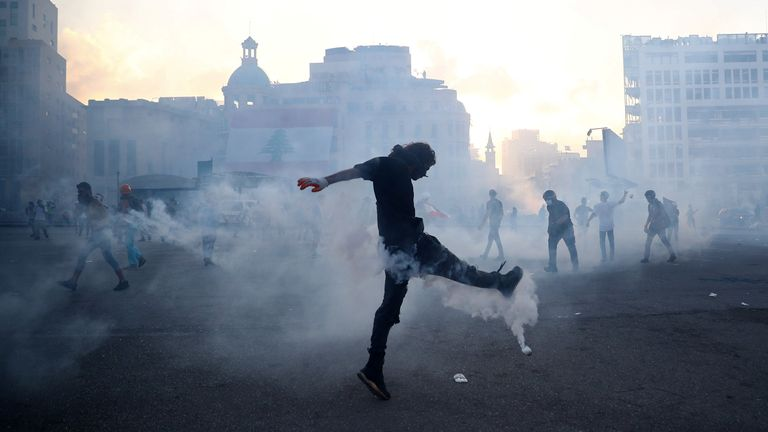 A demonstrator kicks a tear gas canister fired by riot police