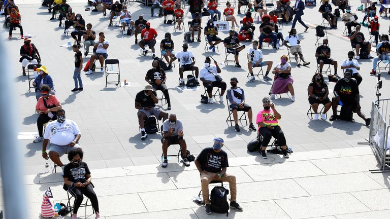 Demonstrators sit in chairs set out for social distancing at the Lincoln Memorial