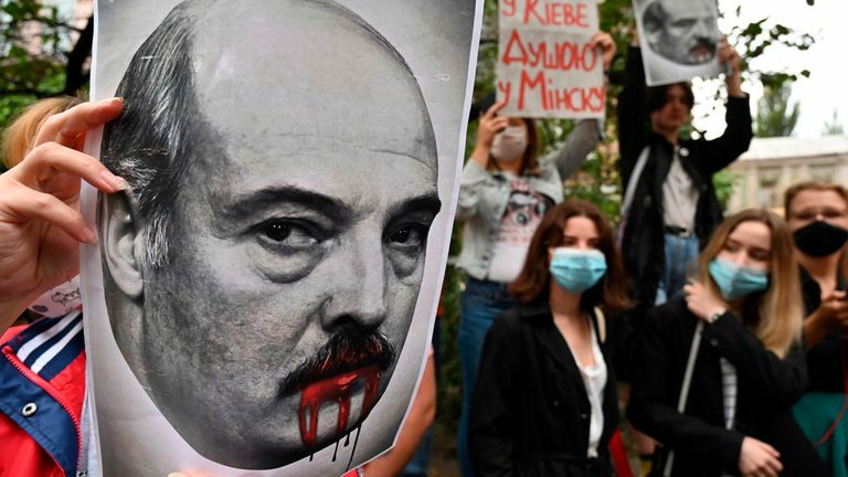 A woman, member of the Belarus diaspora holds a placard depicting Alexander Lukashenko with blood on his mouth and moustache as she with others take part in a rally in support of Belarus people protesting vote rigging in the presidential election, outside the Belarusian embassy in Kiev