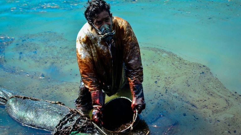 A man scoops leaked oil from the vessel MV Wakashio