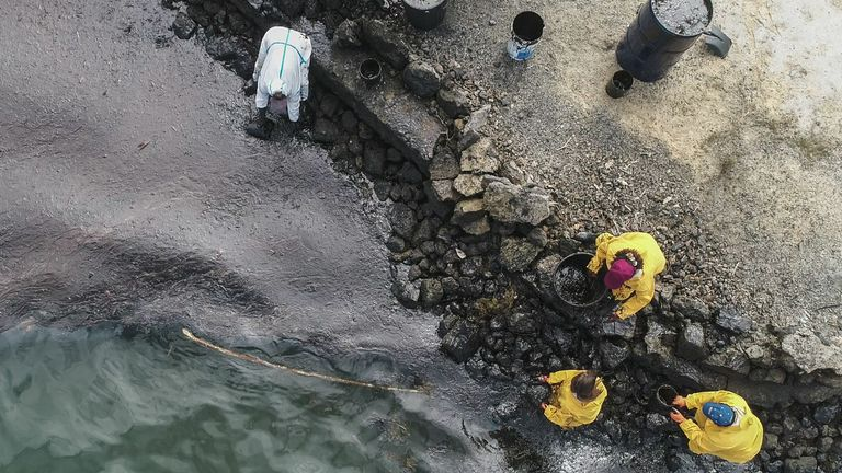 An aerial view of people scooping leaked oil out of the waters off Mauritius