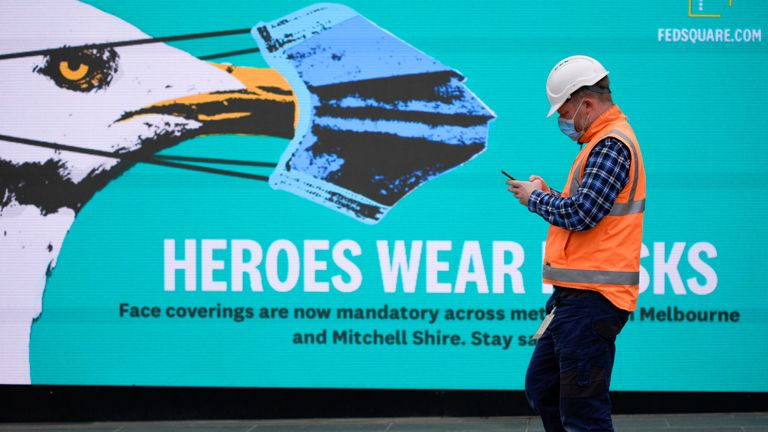 A key workers in Victoria walks past a sign encouraging people to wear masks