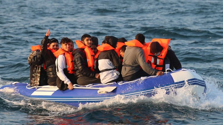 A man gives a thumbs up as he sits with a group of people, thought to be migrants, crossing the Channel in a small boat