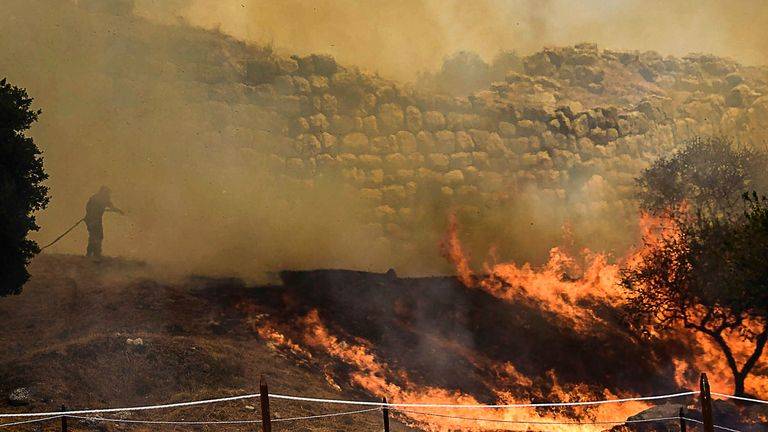 A firefighter works to put out a wildfire near the archaeological site of Mycenae
