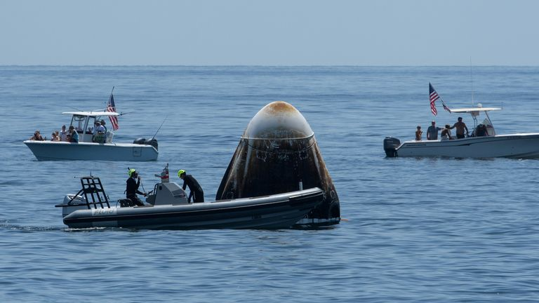 Support teams arrived at the spacecraft just after it landed, with members of the public in private boats looking on