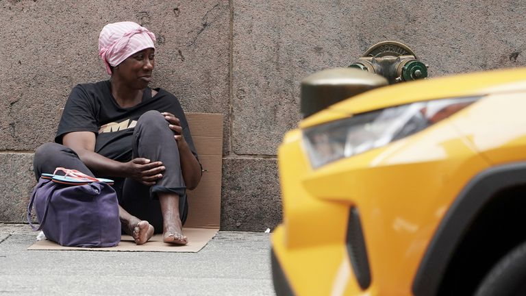 A woman sits on the ground and asks for money in New York following the coronavirus (COVID-19) disease outbreak