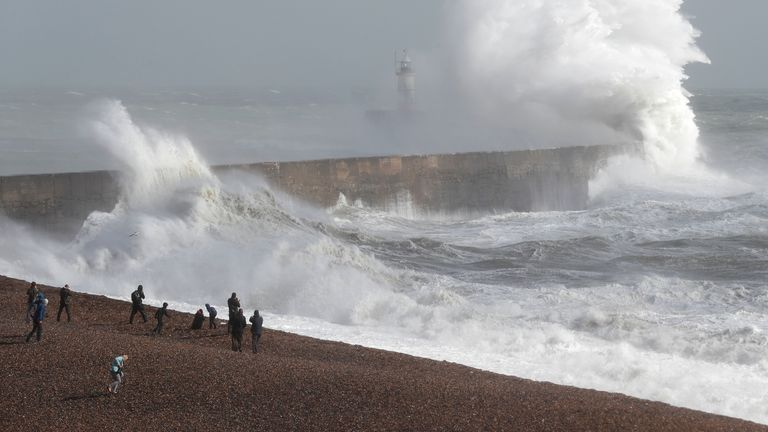 Waves crash over a lighthouse in Newhaven. Beaches are not expected to be packed amid chilly conditions in the UK