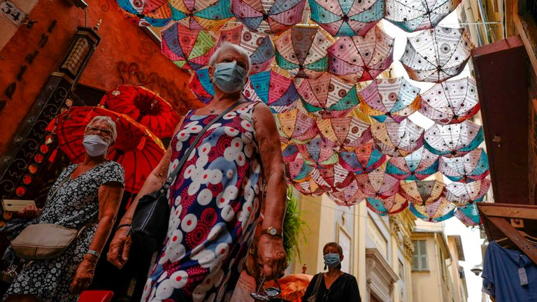 People wearing face masks walk in the French riviera city of Nice, on August 3, 2020