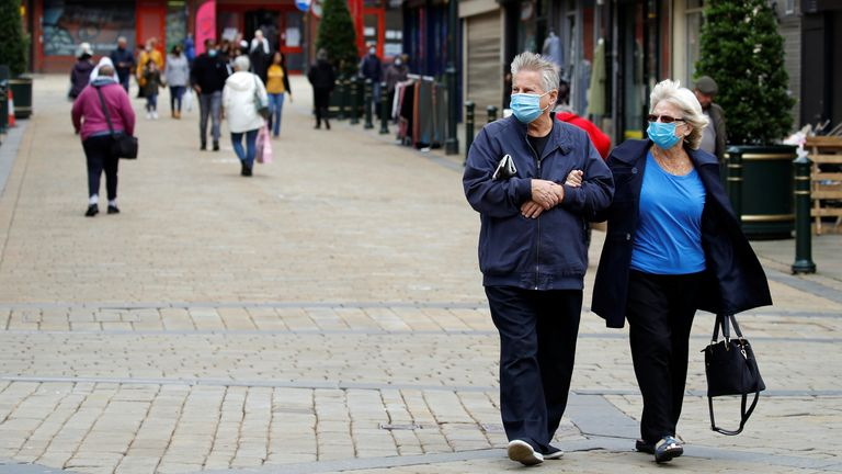 People wear protective face masks as they walk in Oldham, as the town faces local restrictions in an effort to avoid a local lockdown being forced upon the area amid the coronavirus disease (COVID-19) outbreak, Britain July 29, 2020. REUTERS/Phil Noble