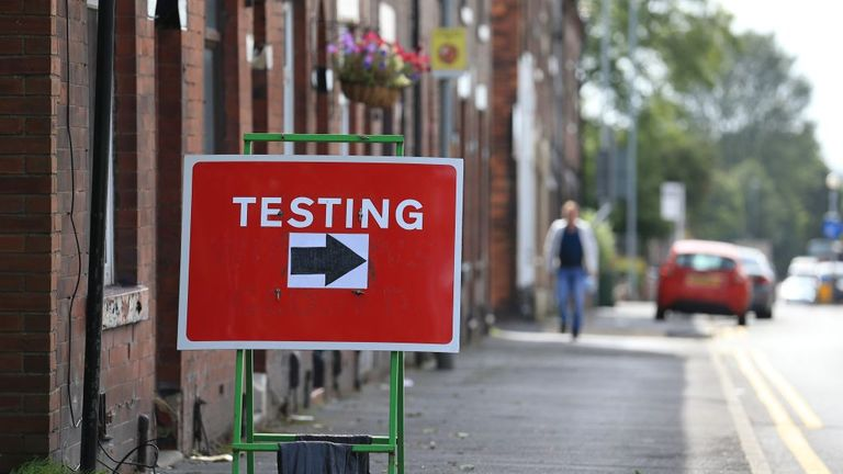 A sign shows where to turn to enter a COVID-19 testing centre in Oldham, Greater Manchester