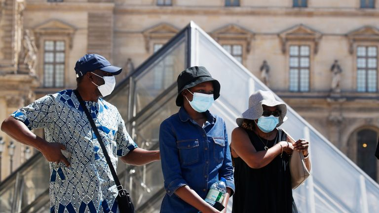 People wearing protective masks walks near the Louvre Museum