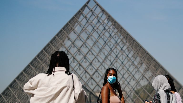 A woman wears a face mask outside the Louvre in the French capital