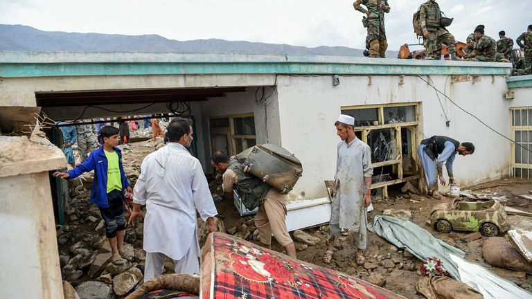 Villagers clear the debris of their houses following severe rainfall in Afghanistan's Parwan province