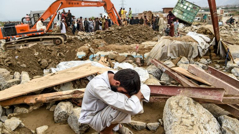 A villager reacts next to his destroyed house as rescuers search for bodies in Parwan province