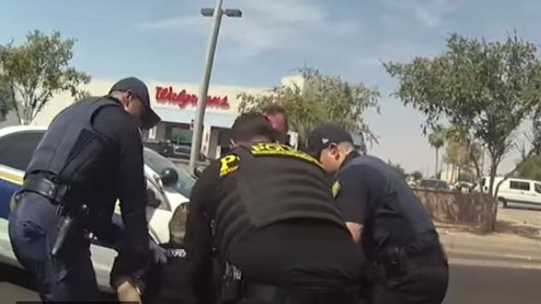 Ramon Timothy Lopez is lifted into a police car by four officers