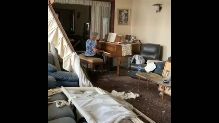 Mother plays the piano among the wreckage of her home