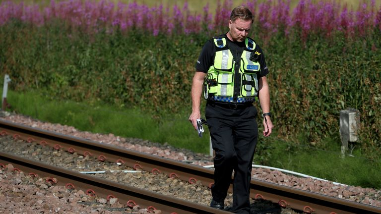 A police officer is seen walking along the track near to the scene where the train derailed