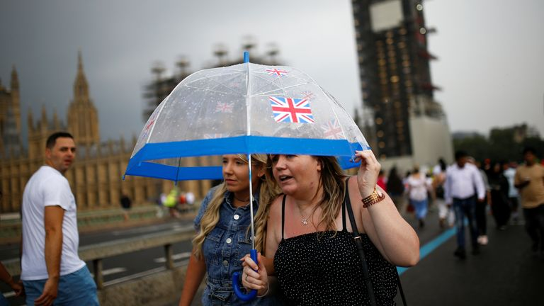 A woman holds an umbrella as she walks on Westminster bridge, in London