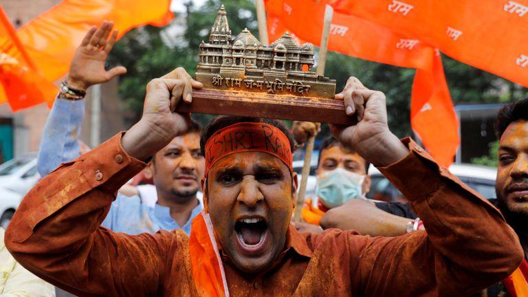 A supporter of the ruling Bharatiya Janata Party holds a model of the proposed temple in Ayodhya to celebrate the stone-laying ceremony