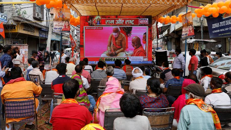 People watch a live screening of the stone-laying ceremony of the Ram temple by Narendra Modi in Ayodhya