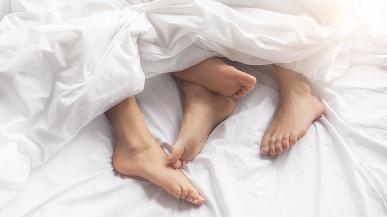Stock image of a young couple in bed