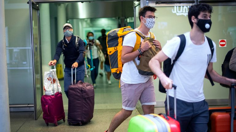 Travellers wearing face masks arrive from Paris to St Pancras Station in London after quarantine restrictions were imposed