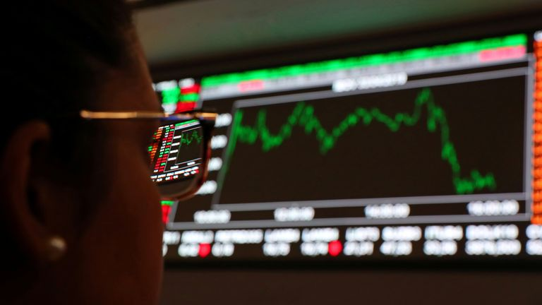 FILE PHOTO: A woman looks at an electronic board showing a graph of recent fluctuations of market indexes