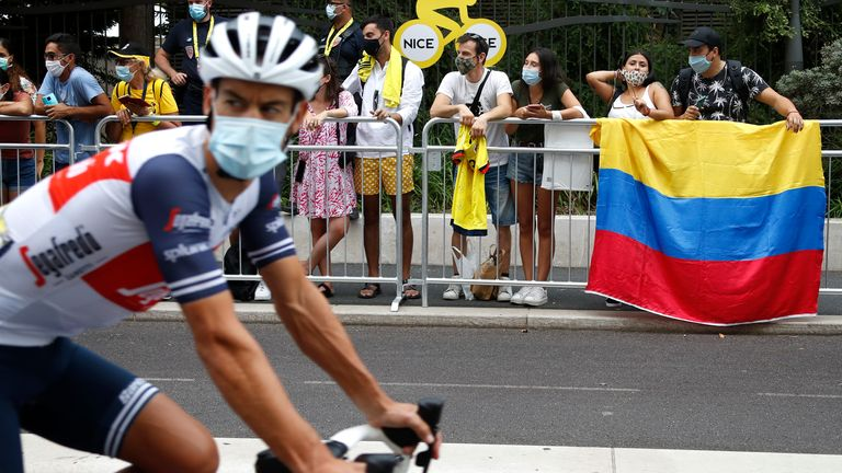 Cycling - Tour de France - Stage 1 - Nice Moyen Pays to Nice - France - August 29, 2020. Spectators hold a Colombian flag as Trek-Segafredo rider Richie Porte of Australia passes by before the start. REUTERS/Eric Gaillard