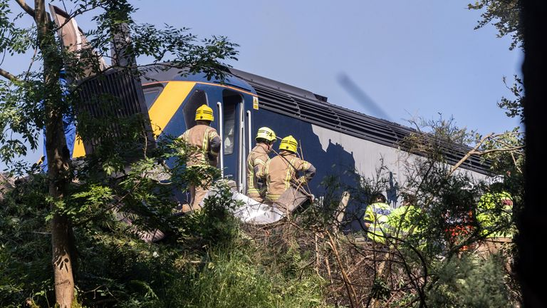 Firefighters are seen outside the train that derailed earlier