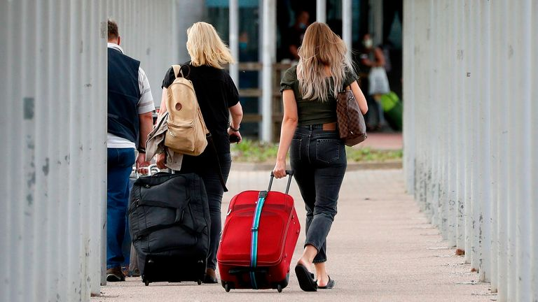 BRITAIN-TRANSPORT-AVIATION-EASYJET Travellers pull their suitcases as they arrive at London Stansted Airport, northeast of London on August 20, 2020 following the decision by British no-frills airline Easyjet to close its operations at the airport from August 31. (Photo by Adrian DENNIS / AFP) (Photo by ADRIAN DENNIS/AFP via Getty Images)
