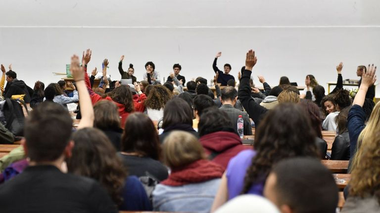 TOPSHOT - Students vote during a general assembly in Nanterre University, west of Paris, on May 15, 2018, a week after having voted an unlimited blockage of their establishment during the partial period, to protest against higher education reforms, introduced by the French government that give public universities the power to set admission criteria and rank applicants. (Photo by GERARD JULIEN / AFP) (Photo credit should read GERARD JULIEN/AFP via Getty Images)