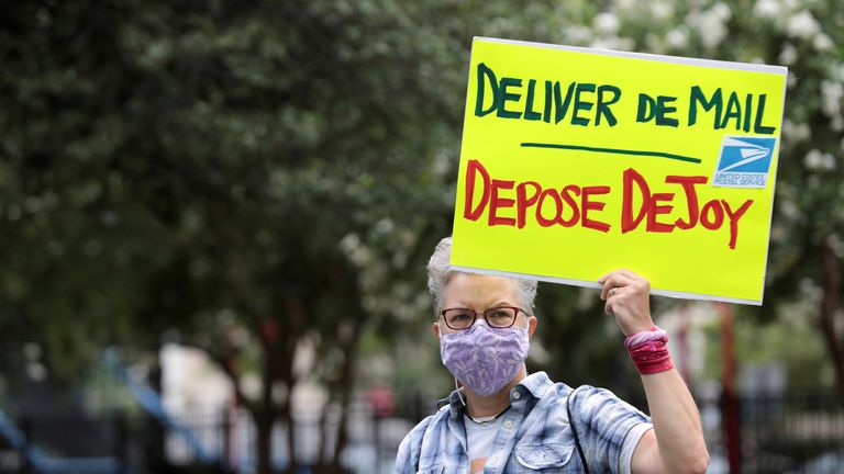 A protester holds a sign opposing US postmaster general Louis DeJoy