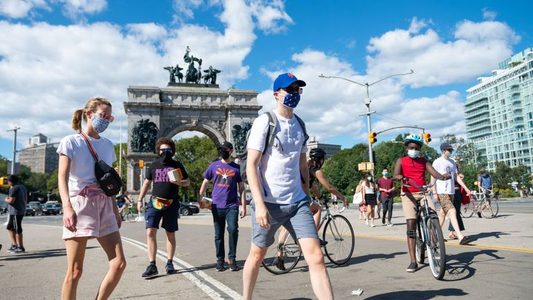 NEW YORK, NEW YORK - AUGUST 30: People wearing masks walks past the Soldiers and Sailors Memorial Arch in Grand Army Plaza, Brooklyn as the city continues Phase 4 of re-opening following restrictions imposed to slow the spread of coronavirus on August 30, 2020 in New York City. The fourth phase allows outdoor arts and entertainment, sporting events without fans and media production. (Photo by Alexi Rosenfeld/Getty Images)