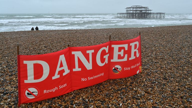 A couple walk on the beach near to a warning sign advising against swimming as a rough sea surrounds the derelict west pier in Brighton on the south coast of England on August 25, 2020. - Wind gusts of 70mph are expected as Storm Francis brings rain and high winds to the country. (Photo by Glyn KIRK / AFP) (Photo by GLYN KIRK/AFP via Getty Images)
