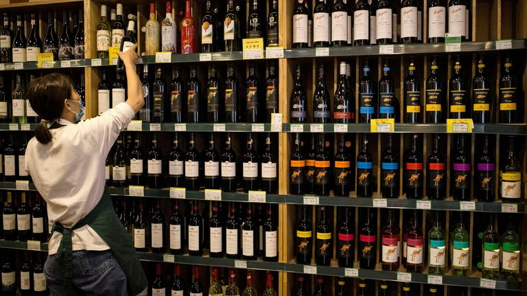 An employee works as Australian-made wine (on display shelves on R) are seen for sale at a store in Beijing on August 18, 2020