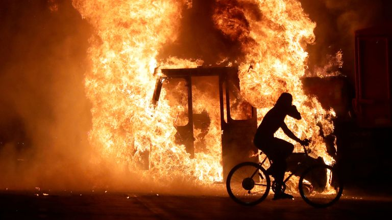 A man on a bike rides past a city truck on fire outside the Kenosha County Courthouse in Kenosha, Wisconsin, U.S., during protests following the police shooting of Black man Jacob Blake August 23, 2020. Picture taken August 23, 2020. Mike De Sisti/Milwaukee Journal Sentinel via USA TODAY via REUTERS MANDATORY CREDIT