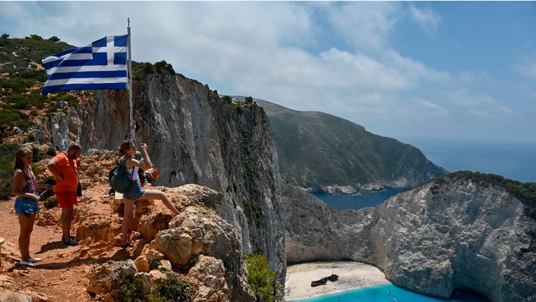 Tourists take pictures and selfies from a rock overlooking the famous Navagio (Shipwreck) beach on the Ionian island of Zakynthos on July 18, 2020. - Usually for the season, there is 20 daily departures for the island's landmark beach, now only four operate daily. (Photo by Louisa GOULIAMAKI / AFP) (Photo by LOUISA GOULIAMAKI/AFP via Getty Images)
